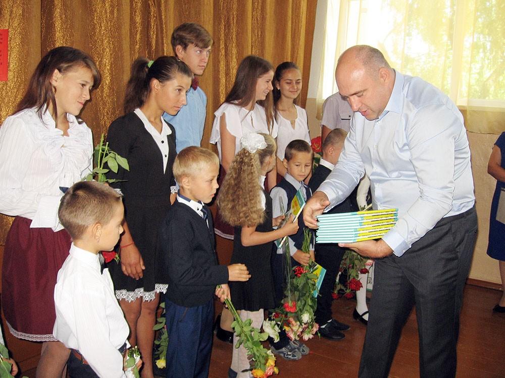 Eduard Bejenari înmânează agende elevilor din clasa I din partea Consiliului Raional